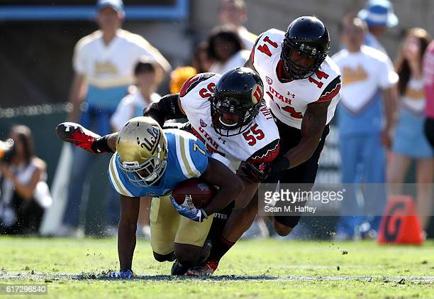 Kavika Luafatasaga and Brian Allen of the Utah Utes tackle Darren Andrews of the UCLA Bruins during the first half of a game at the Rose Bowl on...