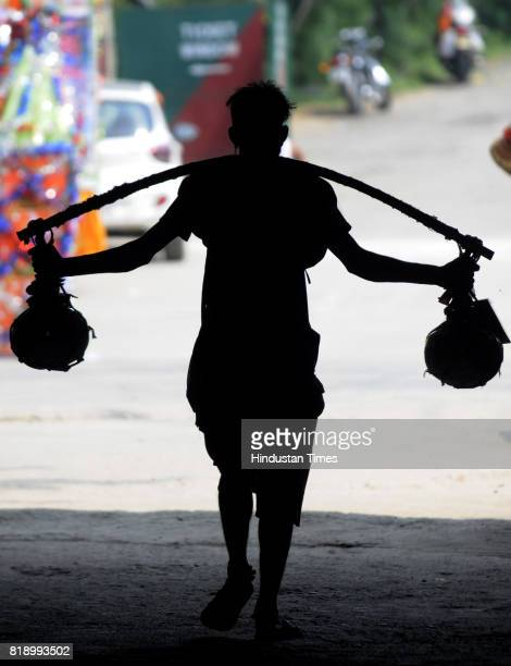 Kawariyas carrying frills such as slagger baseball bat masks which help them in their long foot journey on July 19 2017 in Noida India