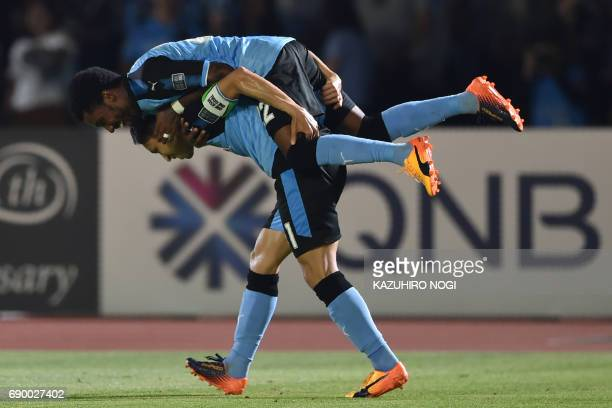 Kawasaki Frontale's forward Rhayner of Brazil is carried by captain Yu Kobayashi after he scored during their AFC Champions League round of 16 second...