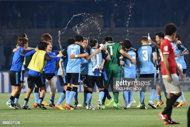 Kawasaki Frontale's players celebrate their win over Muangthong United in their AFC Champions League round of 16 second leg football match between...