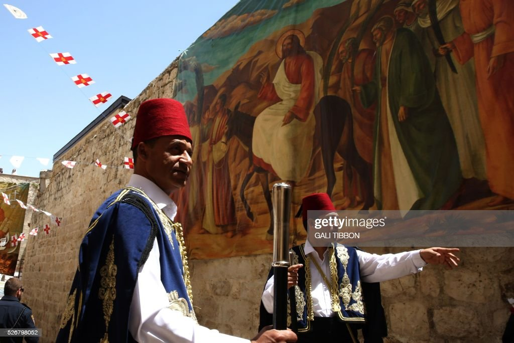 Kawases of the Greek Orthodox patriarchate in traditional Ottoman outfits walk past Easter decorations as they head to the Church of the Holy Sepulchre in Jerusalem's Old City during the Orthodox Christian celebrations of the resurrection of Jesus, on May 1, 2016. / AFP / GALI