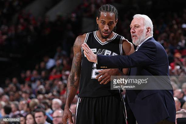 Kawhi Leonard and Gregg Popovich of the San Antonio Spurs talk against the Portland Trail Blazers on December 15 2014 at the Moda Center Arena in...