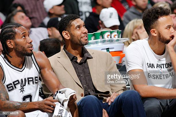 Kawhi Leonard of the San Antonio Spurs and Tim Duncan of the San Antonio Spurs look on from the bench during the game against the Minnesota...
