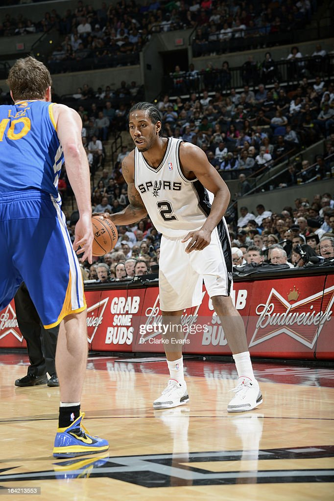 Kawhi Leonard #2 of the San Antonio Spurs dribbles the ball against David Lee #10 of the Golden State Warriors on March 20, 2013 at the AT&T Center in San Antonio, Texas.