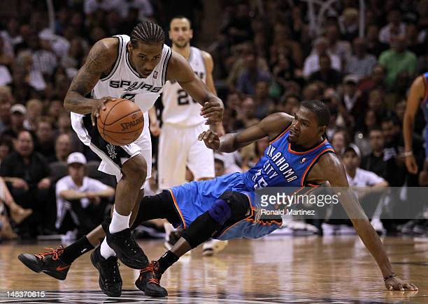 Kawhi Leonard of the San Antonio Spurs dribbles the ball alongside Kevin Durant of the Oklahoma City Thunder in the second half in Game One of the...