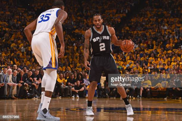 Kawhi Leonard of the San Antonio Spurs dribbles the ball while guarded by Kevin Durant of the Golden State Warriors in Game One of the Western...