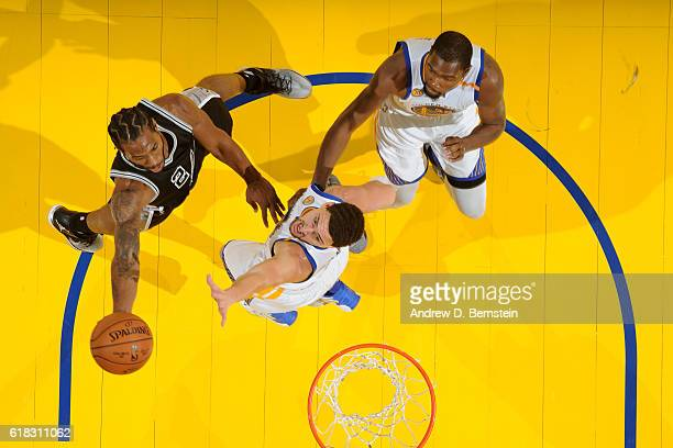 Kawhi Leonard of the San Antonio Spurs drives to the basket against Klay Thompson of the Golden State Warriors on October 25 2016 at ORACLE Arena in...
