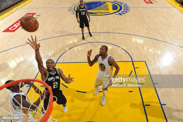 Kawhi Leonard of the San Antonio Spurs drives to the basket and shoots the ball against the Golden State Warriors in Game One of the Western...