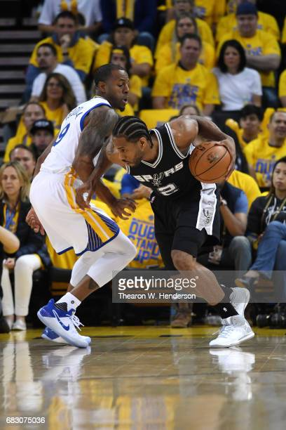 Kawhi Leonard of the San Antonio Spurs drives with the ball against Andre Iguodala of the Golden State Warriors during Game One of the NBA Western...