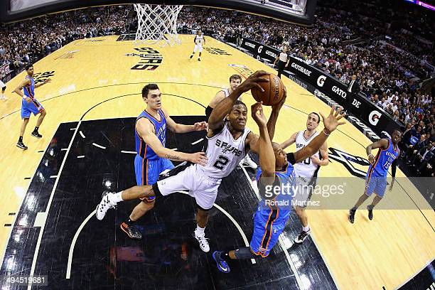 Kawhi Leonard of the San Antonio Spurs goes for a rebound against Caron Butler of the Oklahoma City Thunder in the second half during Game Five of...