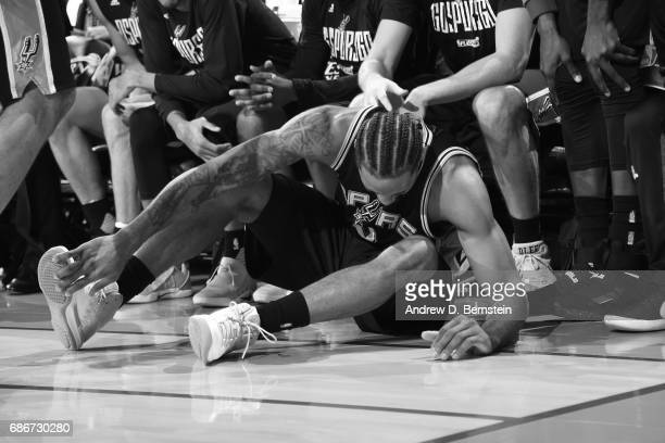 Kawhi Leonard of the San Antonio Spurs grabs his legs after an injury in Game One of the Western Conference Finals against the Golden State Warriors...