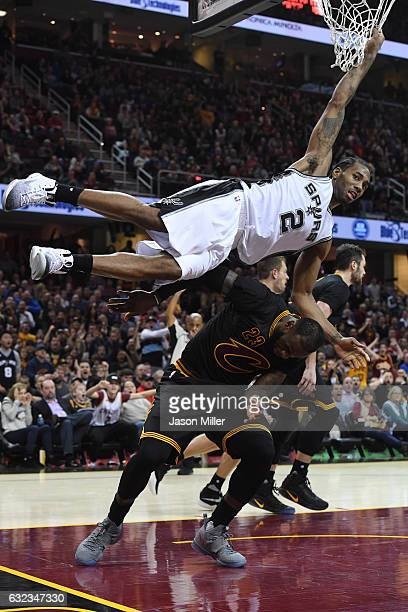 Kawhi Leonard of the San Antonio Spurs hangs on the net to avoid landing on LeBron James of the Cleveland Cavaliers during overtime at Quicken Loans...