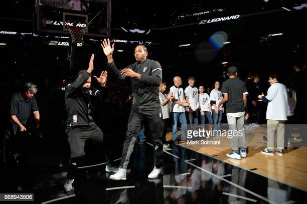 Kawhi Leonard of the San Antonio Spurs highfives his teammates before the game against the Memphis Grizzlies in Game One of Round One during the 2017...