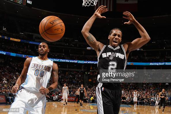 Kawhi Leonard of the San Antonio Spurs looses control of the ball against Darrell Arthur of the Denver Nuggets at Pepsi Center on December 14 2014 in...