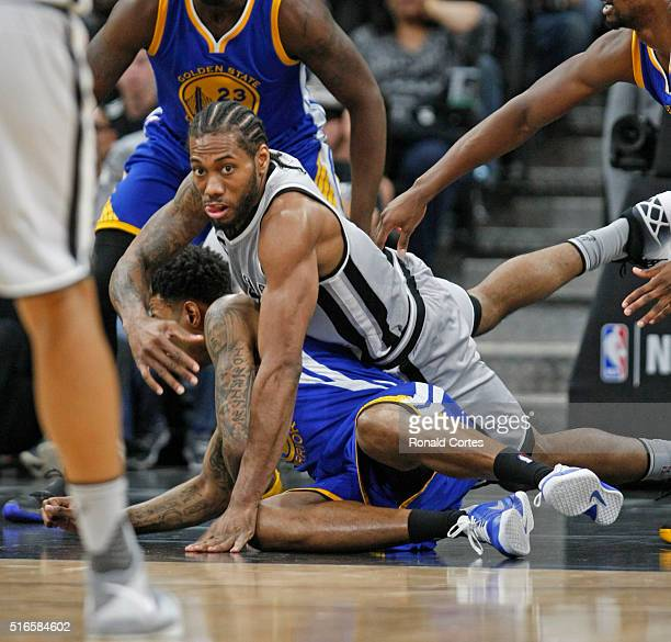 Kawhi Leonard of the San Antonio Spurs passes the ball after diving in front of Brandon Rush of the Golden States Warriors at ATT Center on March 19...