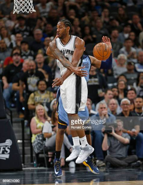Kawhi Leonard of the San Antonio Spurs passes the ball off after driving against the Memphis Grizzlies in Game Two of the Western Conference...