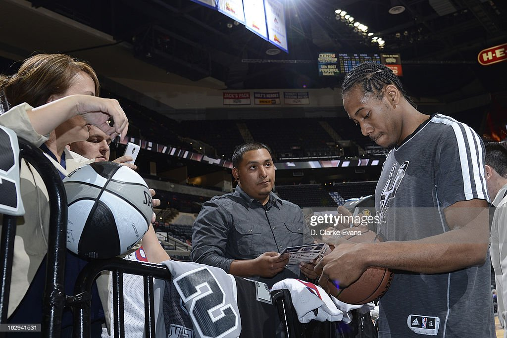 Kawhi Leonard #2 of the San Antonio Spurs signs autographs before the game against the Sacramento Kings on March 1, 2013 at the AT&T Center in San Antonio, Texas.