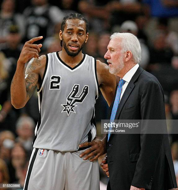Kawhi Leonard of the San Antonio Spurs talks with head coach Gregg Popovich at ATT Center on March 12 2016 in San Antonio Texas NOTE TO USER User...