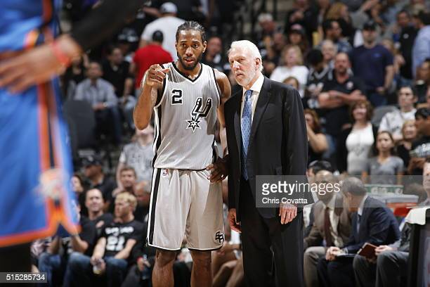 Kawhi Leonard speaks with head coach Gregg Popovich of the San Antonio Spurs during the game against the Oklahoma City Thunder on March 12 2016 at...
