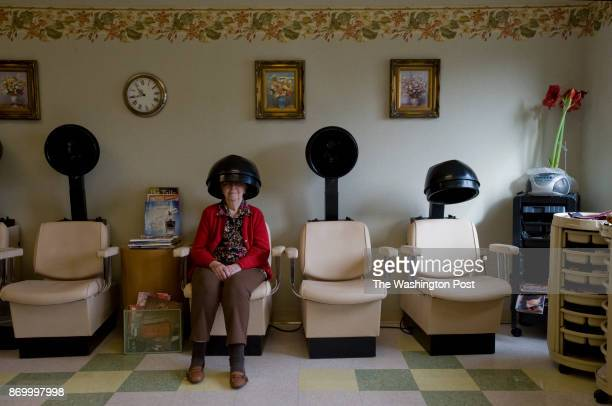 Kay Guiles waits for her hair to dry during a visit to the salon in the retirement village where she and her husband George reside in Silver Spring...