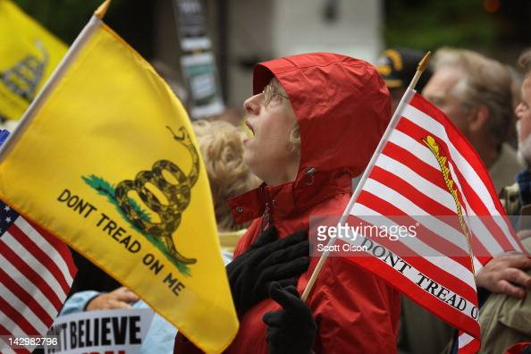 Kay Herrmann sings the National Anthem at the start of a Tea Party rally which was held to protest President Barack Obama's proposed 'Buffett rule'...