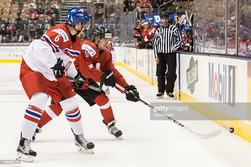 Kay Schweri #18 of Switzerland battles for the puck against Lukas Klok #6 of Czech Republic during the 2015 IIHF World Junior Championship on December 27, 2014 at the Air Canada Centre in Toronto, Ontario, Canada.