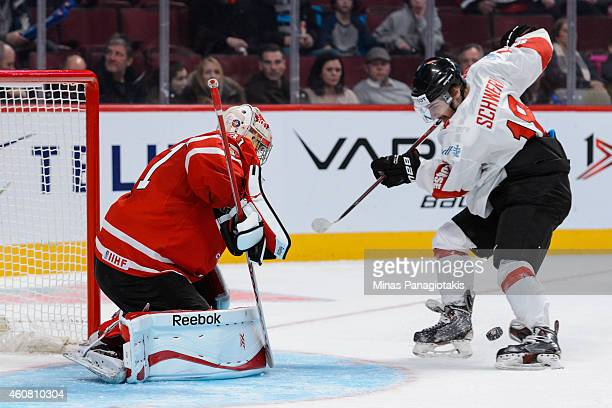 Kay Schweri of Team Switzerland is unable to control the puck near goaltender Zachary Fucale of Team Canada during the 2015 IIHF World Junior Hockey...