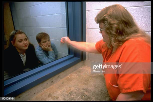 Kay Weekley touching glass separating her from her children Joe Amanda visiting their mom battered wife in prison for 1992 murder of their dad her...