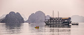A kayak paddles past a junk in Ha long Bay, Vietnam