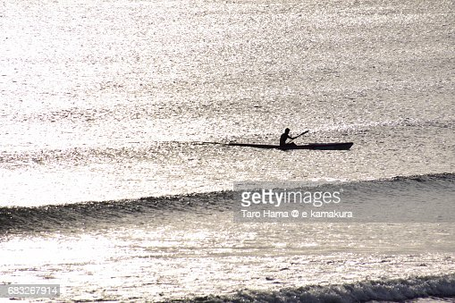 A kayak riding on the wave in the sunset : ストックフォト