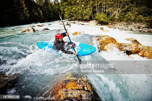 Kayaker entering white water rapids