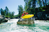 Kayaker on top of rock in rapids smiling