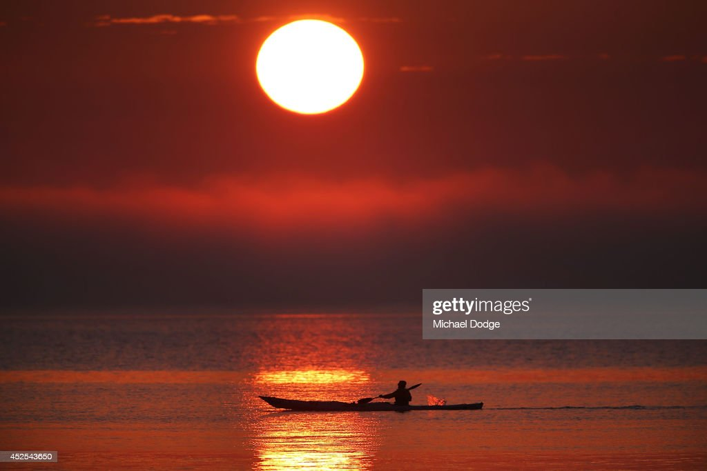 A Kayaker paddles near the Frankston foreshore as the sun sets over the low lying cloud of fog on July 22, 2014 in Melbourne, Australia. Low temperatures and heavy fog hit Melbourne on Tuesday morning and again on Wednesday, causing Tuesday's flight delays.