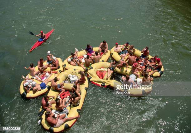 Kayaker Passes Party of Rafters