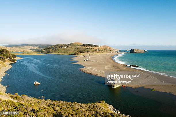 Kayakers beached at Goat Rock Beach by outlet of Russian River below Jenner in Sonoma State Coast Park.