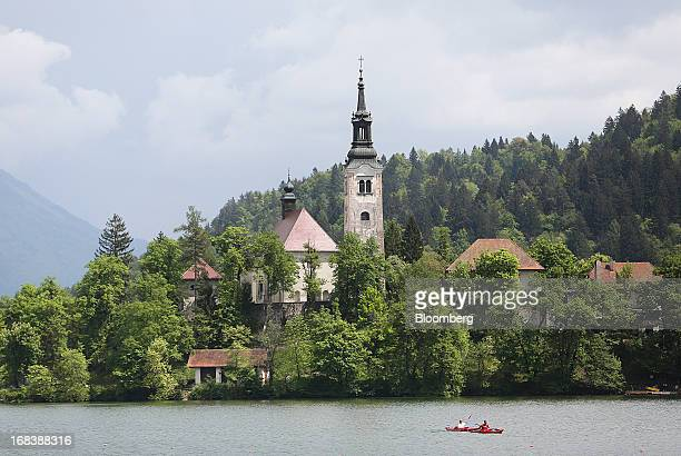 Kayakers paddle past the church of the Assumption of Mary a pilgrimage site and tourist attraction on Lake Bled in Slovenia on Wednesday May 8 2013...
