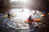Kayakers rowing in still lake