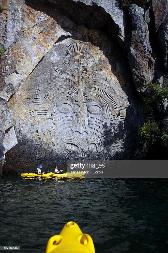 Kayakers visit the maori rock carvings at mine bay lake