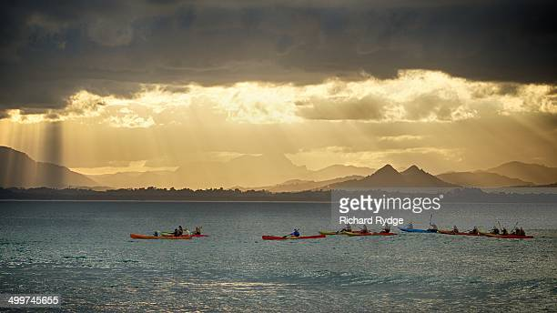 Kayakers watch for whales as the sun sets