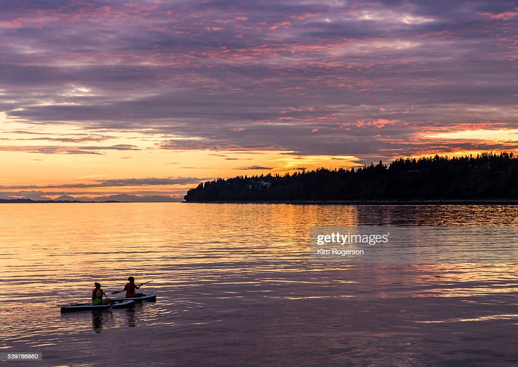 Kayakers watching the setting sun at White Rock Beach, Canada