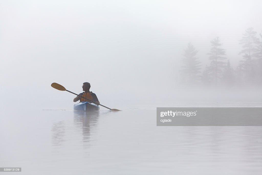 Caiaque no início da manhã de nevoeiro : Foto de stock