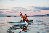 Adventurous woman is sea kayaking near Downtown Vancouver, British Columbia, Canada, during a vibrant sunrise. Concept of Adventure and Fitness