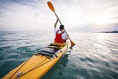 Rear view of man kayaker paddling.