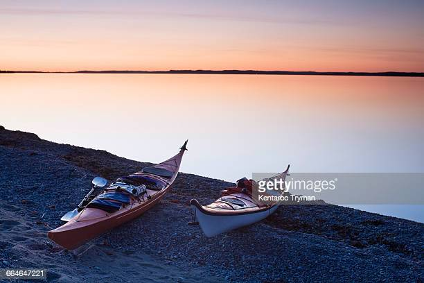 Kayaks moored on field by calm lake during sunset