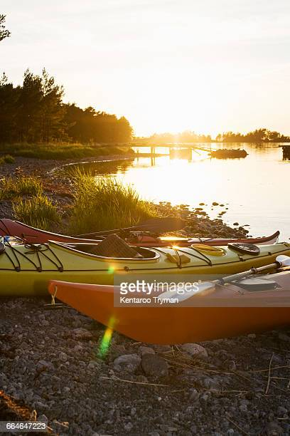Kayaks moored on lakeshore during sunset