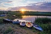 Kayaks on river bank. Beautiful sunset on river.
