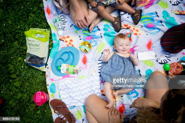 Kayla Brennick at bottom of frame has a mid afternoon picnic in Tommy's Park with her 4montholddaughter Leah her friend Brittany Gagnon and the...