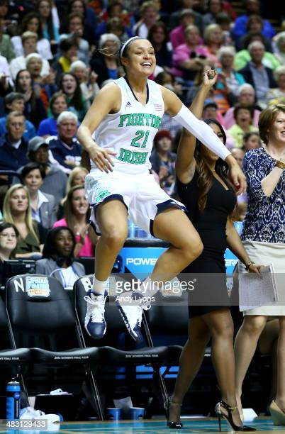 Kayla McBride of the Notre Dame Fighting Irish jumps in celebration on the bench in the second half against the Maryland Terrapins during the NCAA...