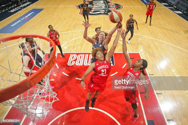Kayla Pedersen of the Connecticut Sun and Tianna Hawkins and Shatori WalkerKimbrough of the Washington Mystics go up for a rebound during a WNBA game...
