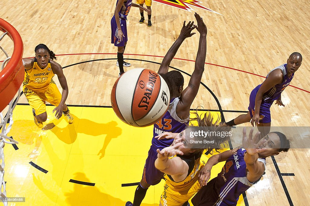 Kayla Peterson of the Tulsa Shock goes to the basket against Nakia Sanford and Candice Dupree of the Phoenix Mercury during the WNBA game on June 17...